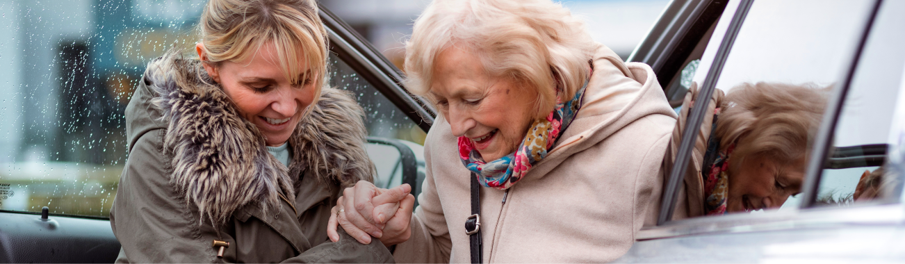 A woman helping an older woman out of a vehicle